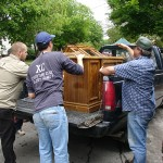 Summer Move Out Project volunteers loading a chest into the back of a pickup truck.