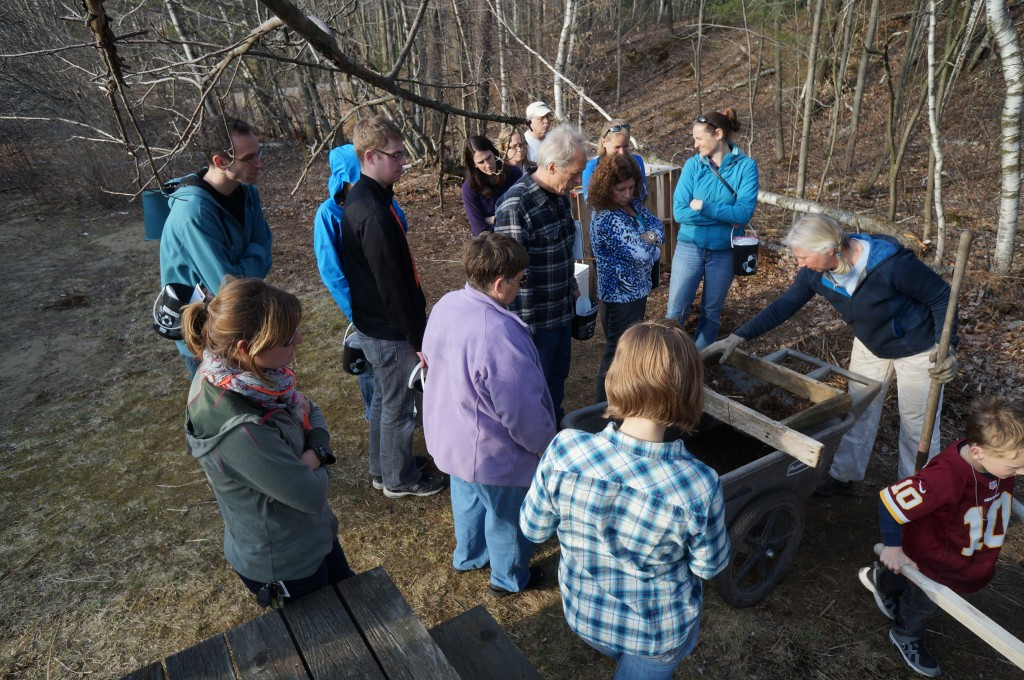 A group of 15 people watching a demonstration at a composting workshop.