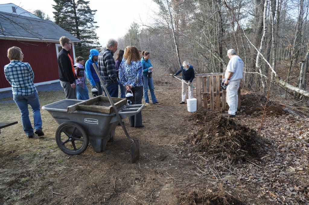 A group of 10 people standing outside watching a composting demonstration.