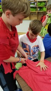 Two 2nd graders at C.P. Smith Elementary School in Burlington turning their unwearable t-shirts into a reusable shopping bag.