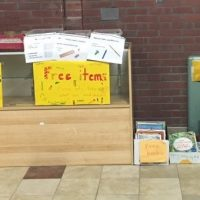 "Boxes and shelves of books and materials are marked with signs saying ""free items"""