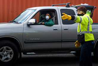 A CSWD employee wearing a cloth mask shows a man in a pickup truck where to drop off items at the dump
