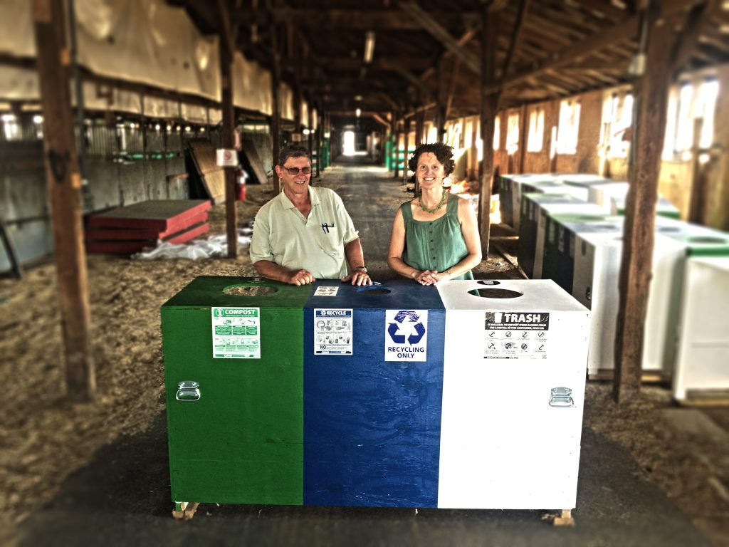 Bob and Robin stand behind a three-bin sort station inside of a large barn.