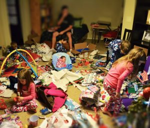 Living room on Christmas morning, strewn with wrapping paper and gifts.