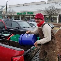 A woman smiles for the camera as she empties compost into a container