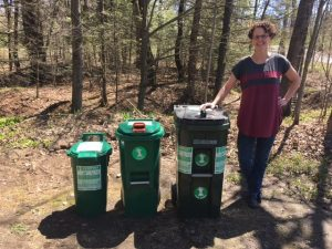 A woman standing next to three composting bin options outdoors.