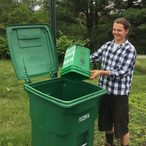Man empties green food scrap bucket into large green toter.