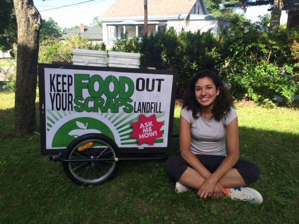 A girl sits on the ground next to a bicycle cart to collect food scraps