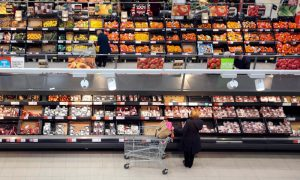 Overhead view of woman with shopping cart browsing meat aisle in grocery store.