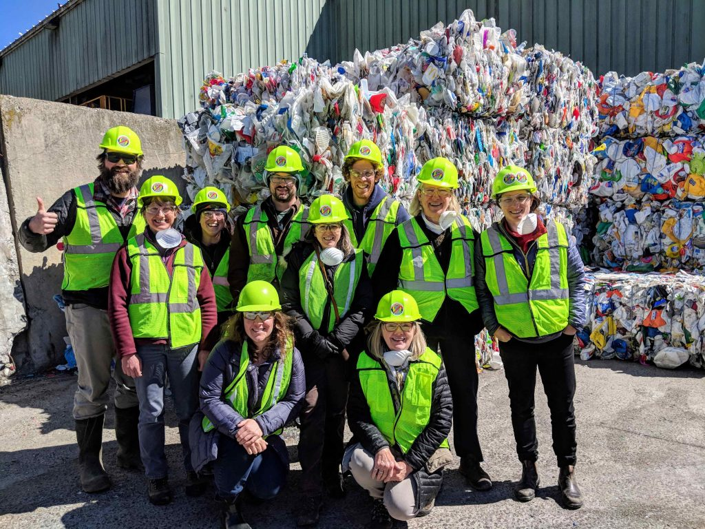 A group of people in safety vests and helmets standing in front of baled material