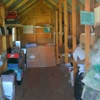 Inside of a shed with packaging materials on the ground and on shelves