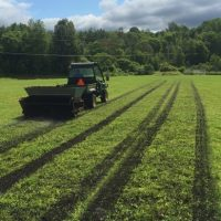 field with tractor spreading topsoil