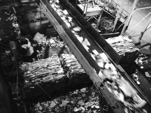 Black and white photo of a conveyor and bales at the MRF.