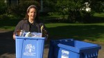A woman holds a blue bin full of recyclables