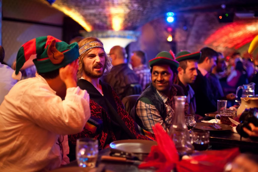 Three men wearing Christmas-themed outfits sitting at a dinner table.