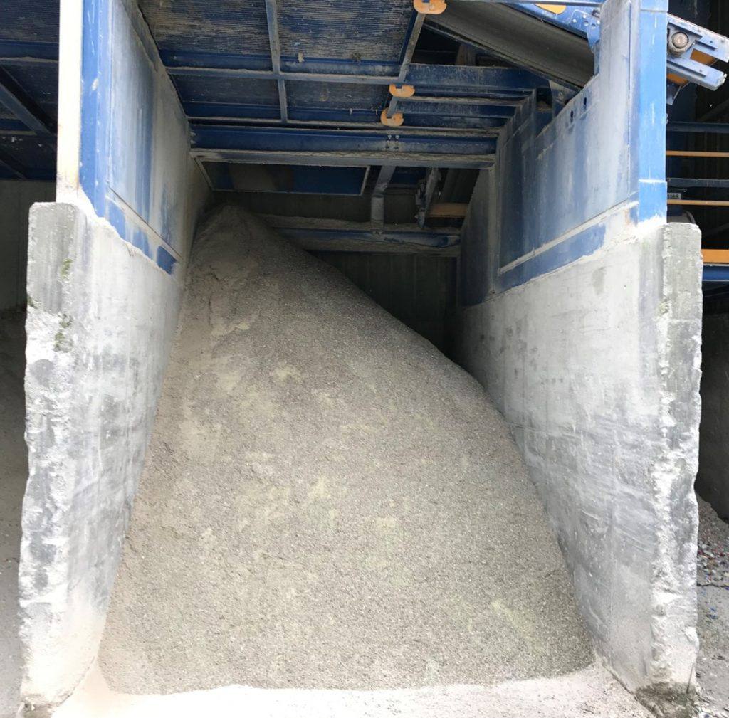 A large mound of granular material sits in concrete storage