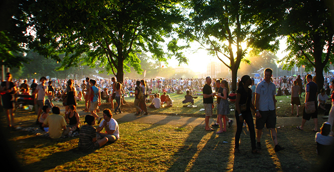 Festival-goers sitting on grass and standing around as sun sets behind them.