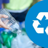 Hand holding plastic bottle next to recycling symbol.