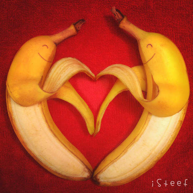 Two bananas with drawn-on smiley faces against a red background