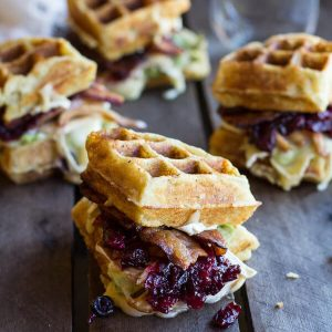 Waffle sandwiches on a wood table.