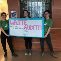 "three people holding a sign that reads ""Waste Audit"""