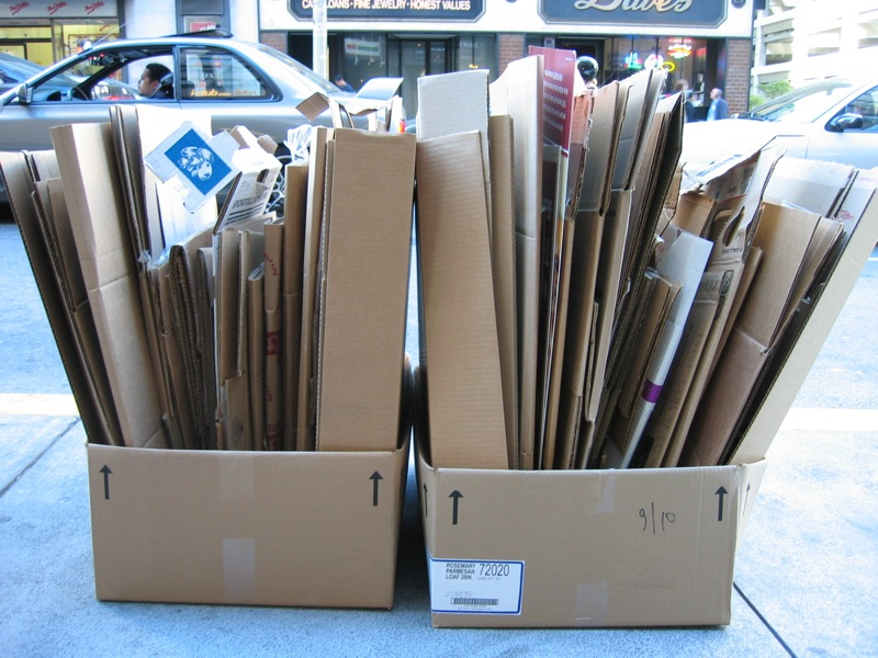 Two boxes of cardboard filled with flattened down cardobard boxes