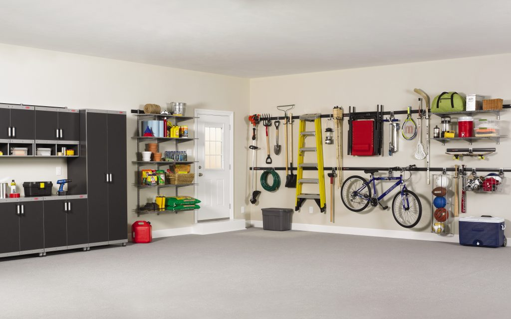 A well organized garage with a clean floor and equipment hanging on the walls.