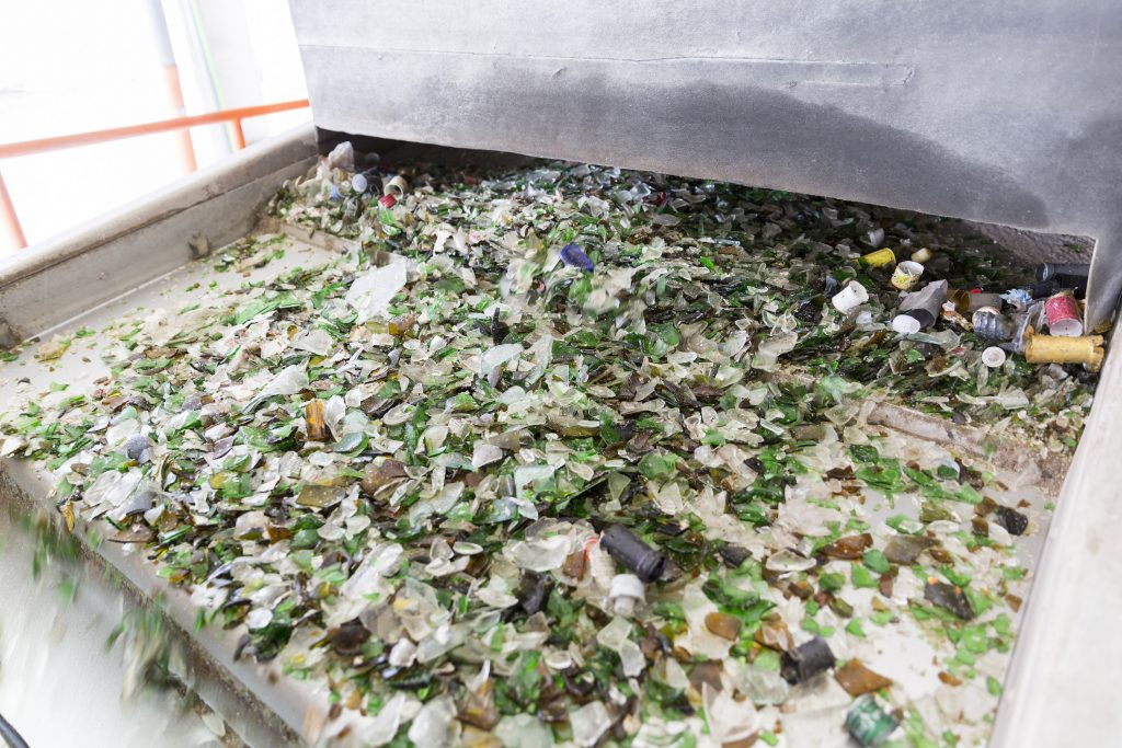 Broken glass bottles and jars at a typical materials recovery facility on a belt so that they can be further sorted and crushed.