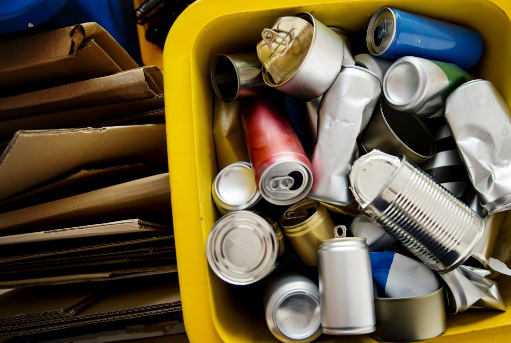 A variety of cans and cardboard in a recycling bin.