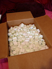 A cardboard box filled with packing peanuts.