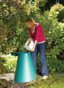 Woman putting food scraps into a Green Cone digester.